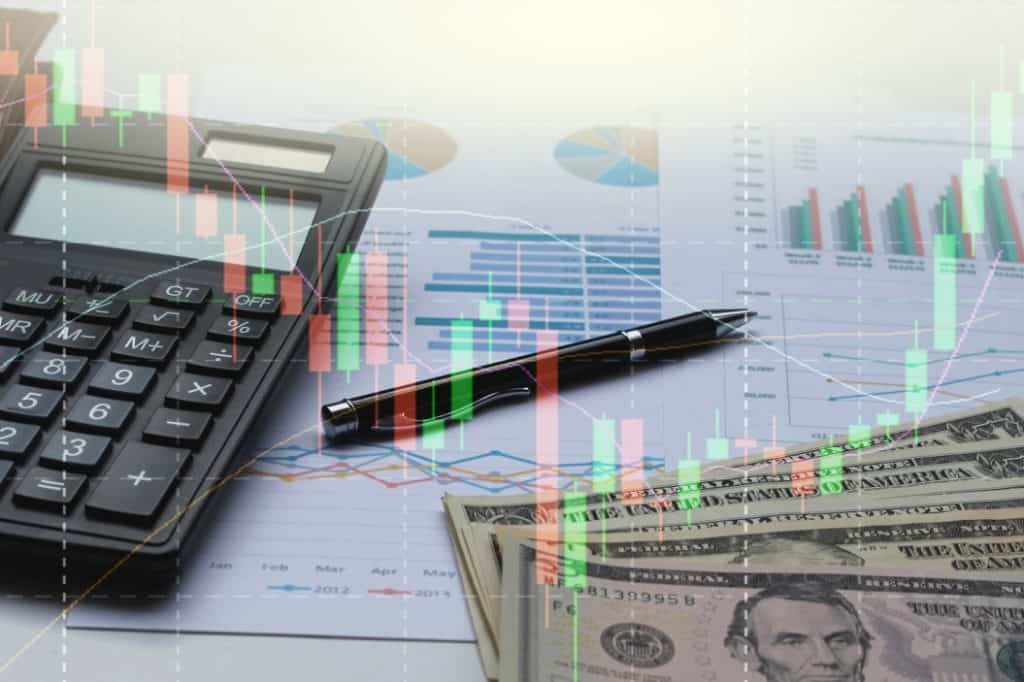 double exposure of business calculator, dollar bills, financial graph, and pen on office desk overlaid with image of stock chart