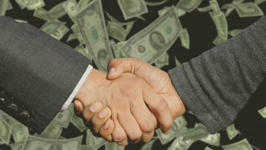 Businessmen shaking hands with money in background