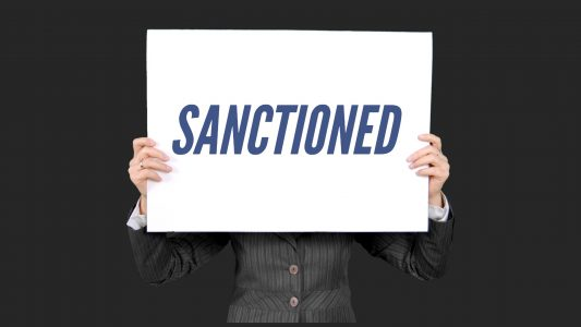 Two hands holding white sign displaying in all caps the word SANCTIONED