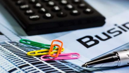 Calculator, paper clips, pen, and business documents