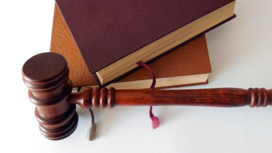 Wood judge's gavel resting on white desk in front of two stacked, brown, hard covered books