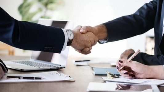Image of people shaking hands in a meeting